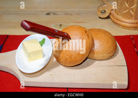Traditional Baltic food - bread rolls and a knob of butter on a wooden chopping board, with a flagon of beer in - Stock Photo