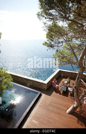 Guests on deck near the Cliff Pool, Aman Sveti Stefan, Sveti Stefan, Budva, Montenegro - Stock Photo