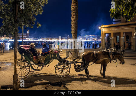 Calesh (horse drawn carriage) on the edge of Place Jemaa el-Fna in Marrakech (Marrakesh) at night - Stock Photo