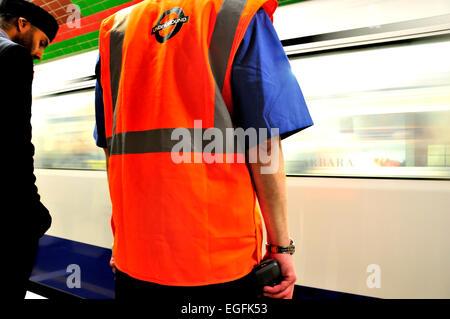 London, England, UK. London underground / tube station employee and passenger on the platform - Stock Photo