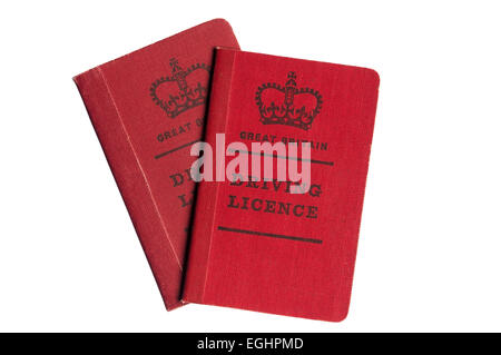 A pair of old style red cloth covered British driving licences. - Stock Photo
