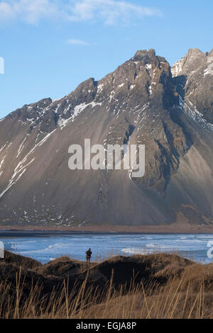 Photographer capturing dramatic scenery with black sand dunes, beach and mountains at Vestrahorn, South Iceland - Stock Photo