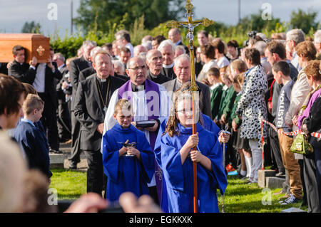 A funeral cortege enters a church graveyard lead by a girl holding a crucifix, an altar boy and a Roman Catholic - Stock Photo
