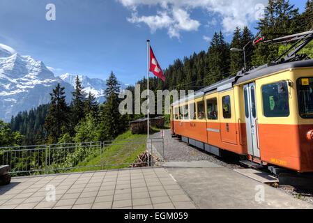 Train leaving station at Grutschalpin in the Jungfrau Region of the Bernese Oberland of Switzerland headed to Murren. - Stock Photo