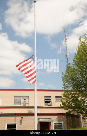American flag flies at half- staff next to a fire station in North Adams Massachusetts. - Stock Photo