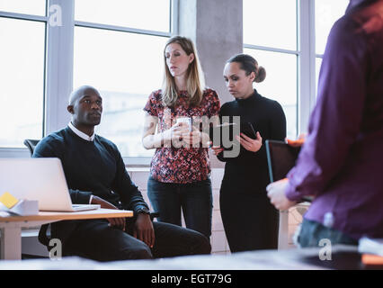 Business people having informal meeting in office. Diverse team of young people discussing work. - Stock Photo