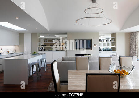 View from dining area towards kitchen and living area beneath curved ceiling with simple modern chandelier in UK - Stock Photo