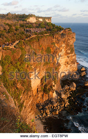 Tourists along the cliffs next to the Ulu Watu temple Pura Luhur. Bali. Uluwatu Temple is a Hindu temple set on - Stock Photo