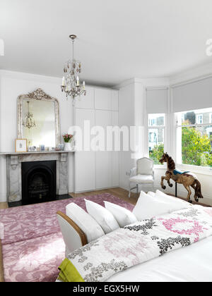 Marble fireplace in spacious white bedroom, UK home - Stock Photo