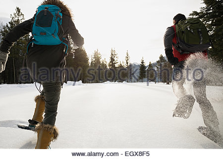 Friends running in snowshoes in snowy field - Stock Photo
