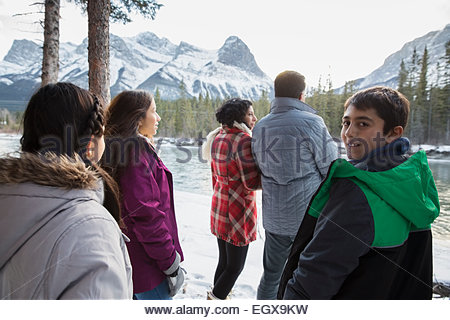 Family looking at snowy mountains at riverside - Stock Photo