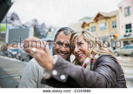 Smiling couple taking selfie outdoors - Stock Photo