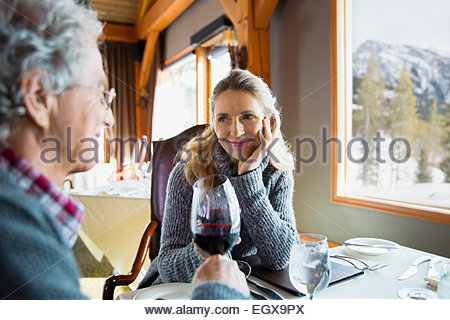 Couple toasting wine glasses at restaurant table - Stock Photo