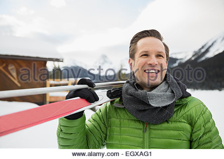 Smiling man with cross-country skis in snow - Stock Photo