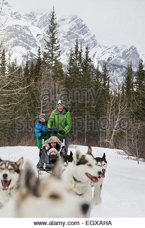 Family dogsledding below snowy mountain - Stock Photo