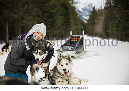 Portrait of girl hugging dogsled dog in snow - Stock Photo
