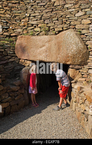 Curious children at the entrance to one of Europe's finest Neolithic  passage graves / La Hougue Bie / Grouville - Stock Photo