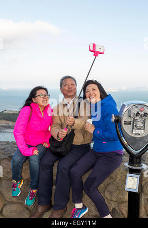 tourists, family, taking selfie, selfie photo, selfie stick, cellphone, Vista Point, north side of Golden Gate Bridge, - Stock Photo