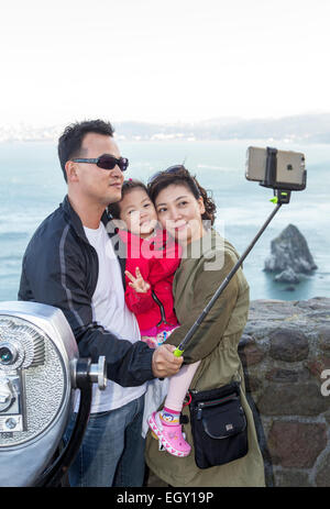 tourists, family, taking selfie, selfie photo, selfie stick, Vista Point, north side of Golden Gate Bridge, city - Stock Photo