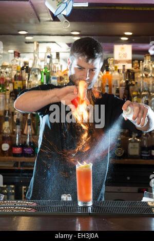 A male barman, bar tender, mixologist makes a fantastic cocktail in a high end restaurant / bar / public house - Stock Photo