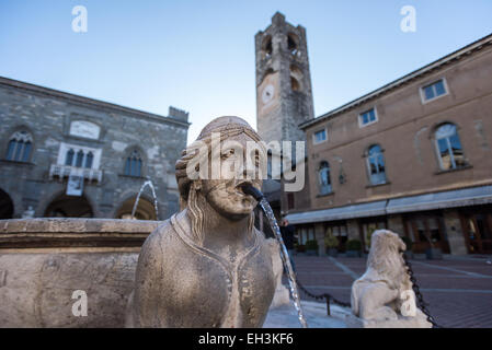 The Contarini fountain in the central square Piazza Vecchia in Bergamo, Italy. Palazzo del Podestà and bell tower - Stock Photo