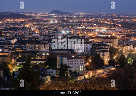 Bergamo, Italy - Aerial view of the old medieval city (Città Alta) and lower Bergamo at night. - Stock Photo