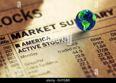 Globe on stock prices in the newspaper - Stock Photo