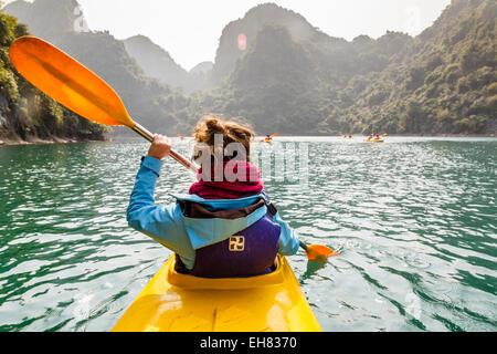 Woman kayaking at Halong Bay, Vietnam, Indochina, Southeast Asia, Asia - Stock Photo