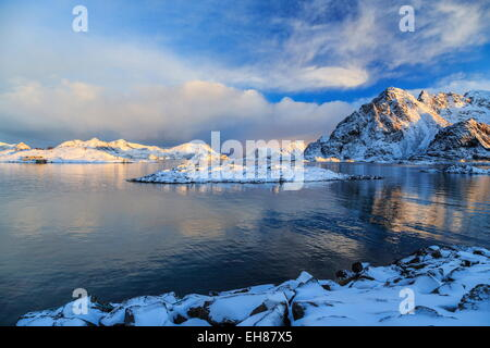 The feeble light of the sunset on a fjord near Henningsvaer covered in snow, Lofoten Islands, Arctic, Norway - Stock Photo