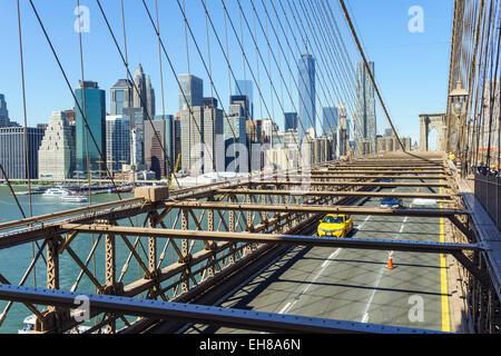 Yellow taxi cab crossing Brooklyn Bridge with the Lower Manhattan skyline behind, New York City, New York, USA - Stock Photo