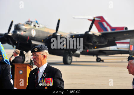 A veteran stands in front of an airworthy Lancaster at The Canadian Warplane Heritage Museum. - Stock Photo