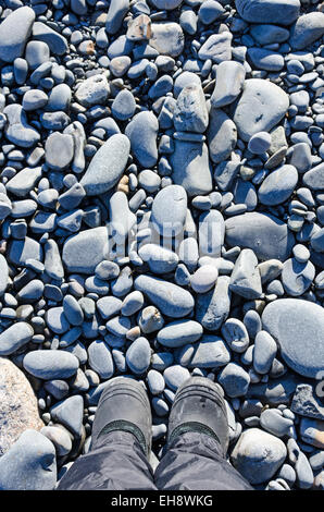 Booted feet standing on a beach of rounded stones, Maine. - Stock Photo