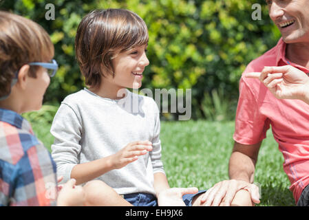 Young boys enjoying outdoor recreation with parents - Stock Photo