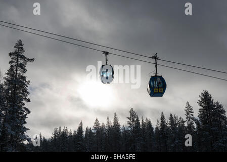 Cable cars in a ski resort moving over trees in front of stormy clouds and sky - Stock Photo