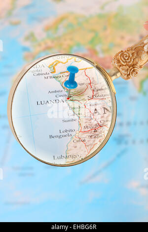 Blue tack on map of Africa with magnifying glass looking in on Luanda, Angola - Stock Photo