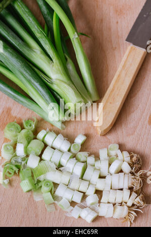 chopped green spring onions on wooden cutting board - Stock Photo