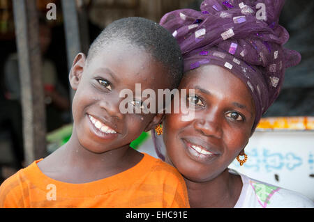 Portrait of Gambian Woman Market Trader and her Son, Serrekunda Market, The Gambia, West Africa - Stock Photo