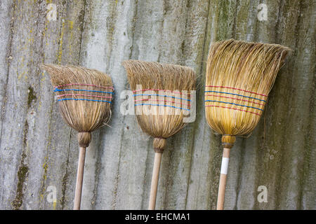 three used brooms on a concrete wall - Stock Photo