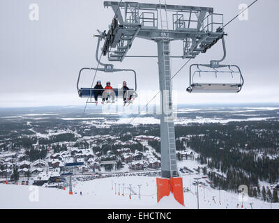A chairlift carrying skiers up the mountain at the ski resort of levi, Lapland Finland in grey overcast conditions - Stock Photo