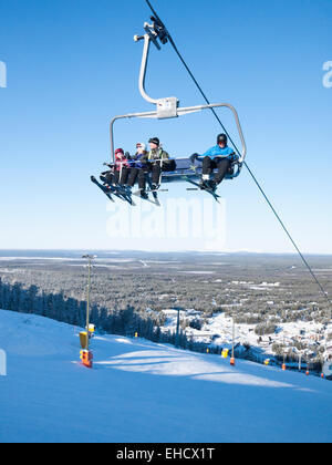 A chairlift carrying skiers up the mountain at the ski resort of Levi, Lapland, Finland in winter sunshine. - Stock Photo