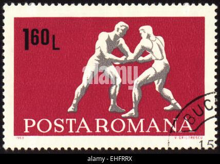 ROMANIA - CIRCA 1969: A post stamp printed in Romania shows wrestling - Stock Photo