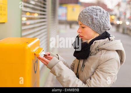 Young lady posting letters. - Stock Photo