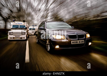 BMW car is chased along a rural road by two PSNI Police Landrovers - Stock Photo