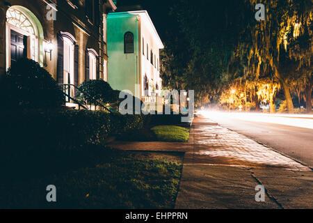 Houses and traffic at night on Drayton Street in Savannah, Georgia. - Stock Photo