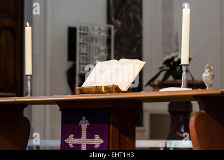 Open Bible and candles on the altar of a church - Stock Photo