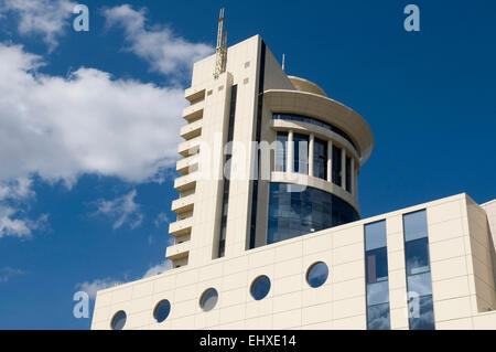 White modern building is situated against the blue sky background. Clouds and sky are reflected in the windows. - Stock Photo