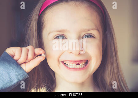 Portrait of smiling little girl with tooth gap holding milk tooth in her hand - Stock Photo