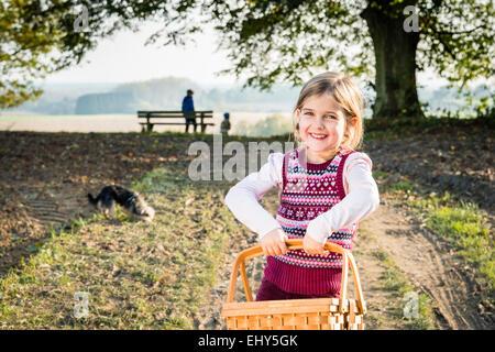 Girl carrying picnic basket - Stock Photo