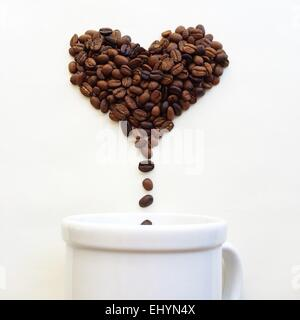 Coffee beans in shape of heart dropping into a coffee cup - Stock Photo