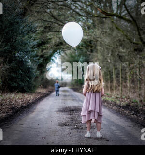 Rear view of girl holding a balloon looking at boy running away from her - Stock Photo
